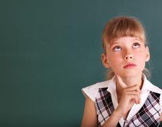 schoolchild near green blackboard. - stock photo