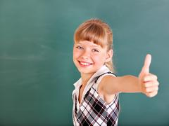 schoolchild in classroom near blackboard. - stock photo