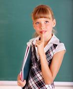 Schoolchild near green blackboard. Stock Photos