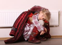 girl in coat warm  near radiator. crisis. - stock photo