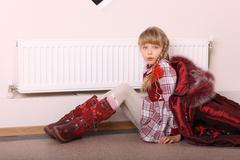Girl in coat warm  near radiator. crisis. Stock Photos