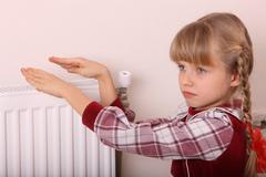 Girl warm one's hands near radiator. crisis. Stock Photos