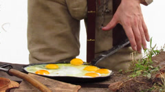 Man cook an omelette in a park Stock Footage