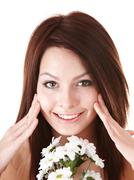 Young woman with flower. facial massage. Stock Photos