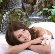 Girl in spa  against waterfall. Stock Photos