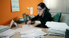 Business woman in office on the phone searching for documents - stock footage
