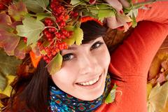girl in autumn orange hat on leaf group and berry. - stock photo