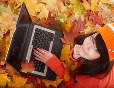 Girl in autumn orange foliage with laptop. Stock Photos