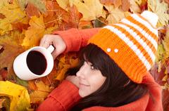 girl in autumn orange leaves with cup coffe. - stock photo