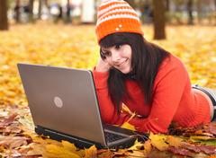 Girl in autumn orange leaves with laptop.fall sale. Stock Photos
