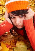 girl in orange hat on leaves.  autumn depression. - stock photo