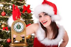 Christmas girl in santa hat and fir tree with alarm clock. Stock Photos