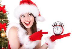 Stock Photo of christmas girl in santa hat and fir tree with alarm clock.