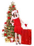 christmas girl in santa hat giving  gift box. - stock photo