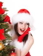 Stock Photo of christmas girl in santa hat with fir tree.