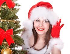 Girl in santa hat  listen near  christmas tree. Stock Photos