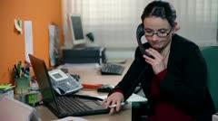 Secretary finishing the phone call not very happy Stock Footage