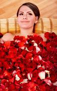 young woman in rose petal swim water. - stock photo