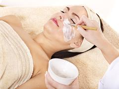 Beautician applying  facial mask by  woman. Stock Photos