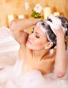Woman washing hair by shampoo . Stock Photos