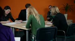 Medium shot of business meeting with young employees writing down information - stock footage