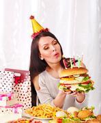 woman eating hamburger at birthday. - stock photo