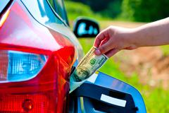 Female hand puts the car into the gas tank one hundred dollars Stock Photos