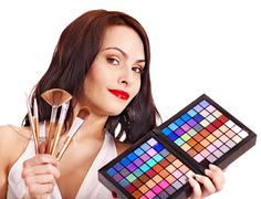 Girl holding eyeshadow and makeup brush. Stock Photos