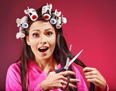Stock Photo of woman wear hair curlers on head.