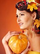 Stock Photo of woman holding autumn fruit.