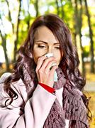 Woman sneezing handkerchief outdoor. Stock Photos