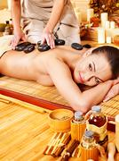 Stock Photo of woman getting stone therapy massage .