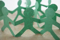 Human silhouettes cut out from green paper Stock Photos