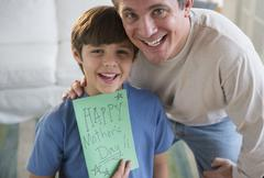 Father and son (8-9) holding Mother's day card Stock Photos