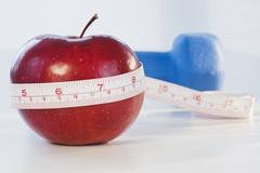 Stock Photo of Apple wrapped in tape measure