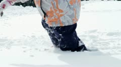 Little girl enjoying while trudging through fresh snow Stock Footage
