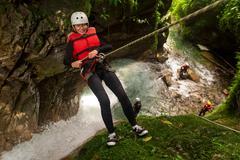 Stock Photo of Senior Woman Descending Into A Waterfall Vertical Shot