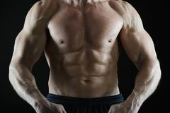 Muscular man flexing his muscles - stock photo