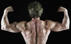 Muscular man flexing his biceps - stock photo