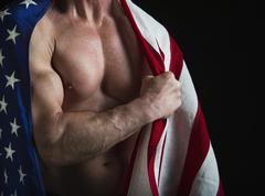 Muscular man wearing American flag as a cape - stock photo