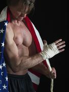 Muscular man wearing American flag as a cape Stock Photos