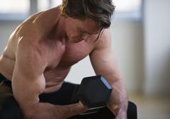 Muscular man lifting free weight - stock photo