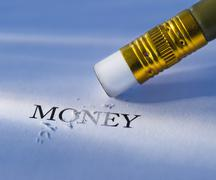 Stock Photo of Studio shot of pencil erasing the word money from piece of paper
