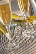 Stock Photo of Flutes with champagne, party horn blowers and paper party hats