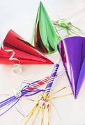 Party horn blowers and paper party hats Stock Photos