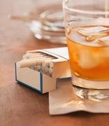 Close up of open cigarette pack and alcohol drink in glass Stock Photos
