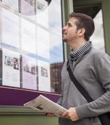 Man with newspaper looking at advert display Stock Photos