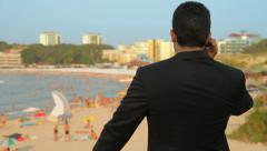 Businessman Talking on Phone looking at beach Vacation HD - stock footage