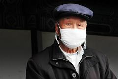 chinese man wear surgical masks - stock photo