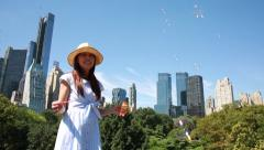 Asian woman girl blowing bubble into the air in urban park - stock footage